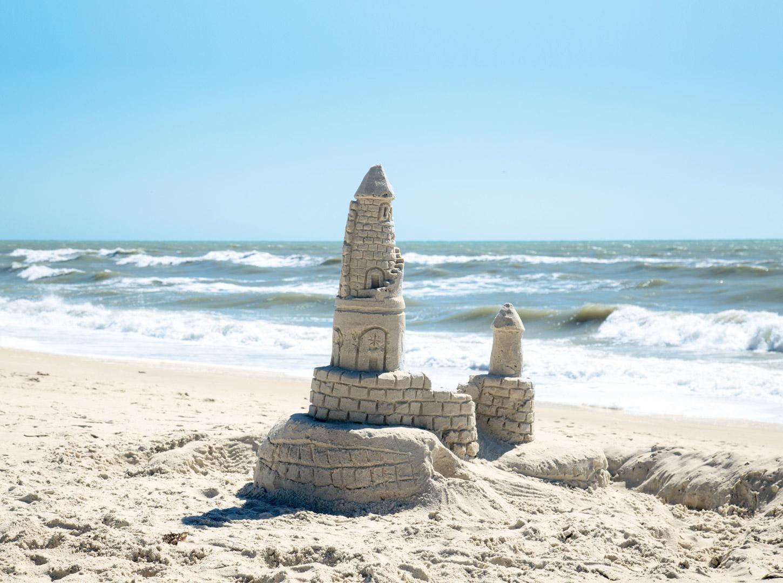 Sandburg_bauen_Meer_Urlaub_Strand_Wellen_Schaum_Sonne_Sommer
