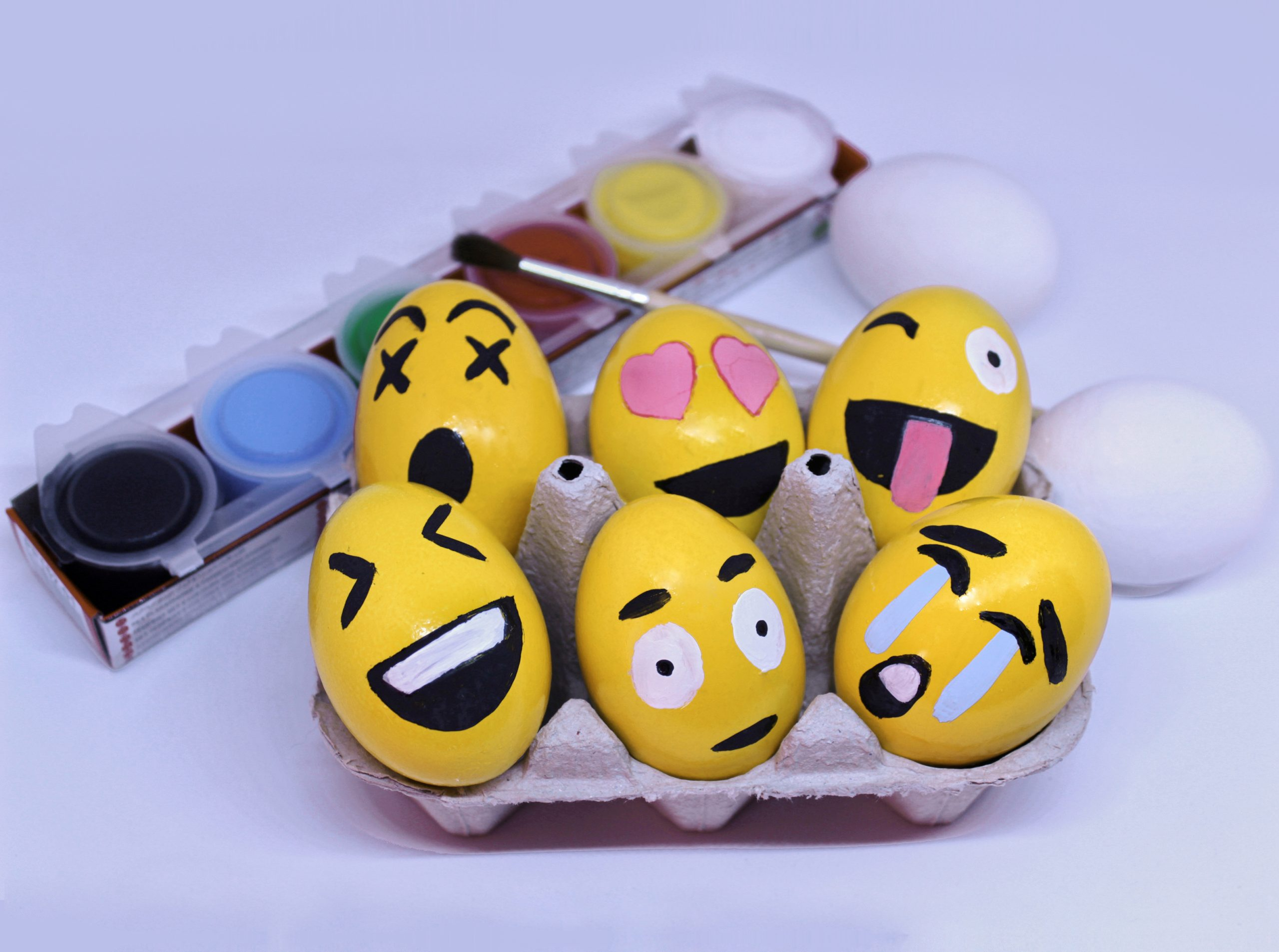 Emoticons Easter Eggs in egg-cup , paints and brush with white background